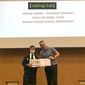 Image of Elijah receiving award for youngest medalist, NOI 2019