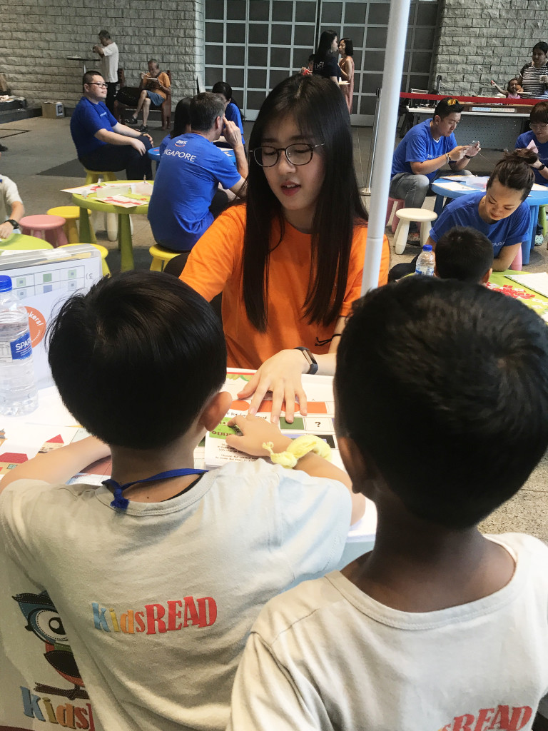 Thinzar, the President of Tiny Thinkers, explaining the Junior Computational Thinking kits to the children at booth.
