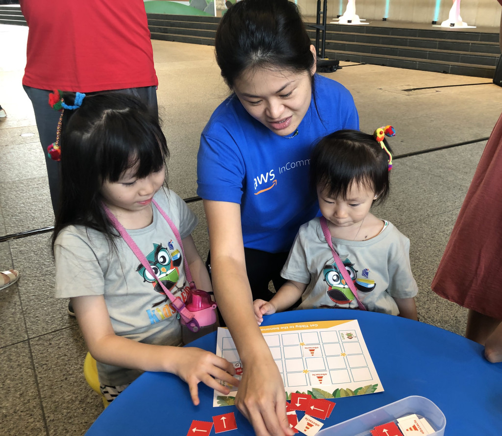 A volunteer from Amazon Web Services guiding two young children through the Junior Computational Kits.