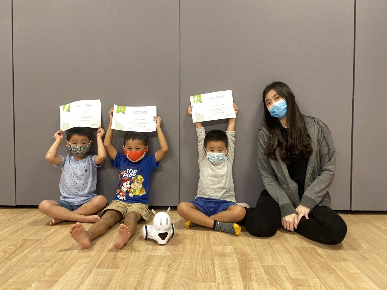 Our Junior Coders graduates proudly showing their certificates with their teacher and Photon robot
