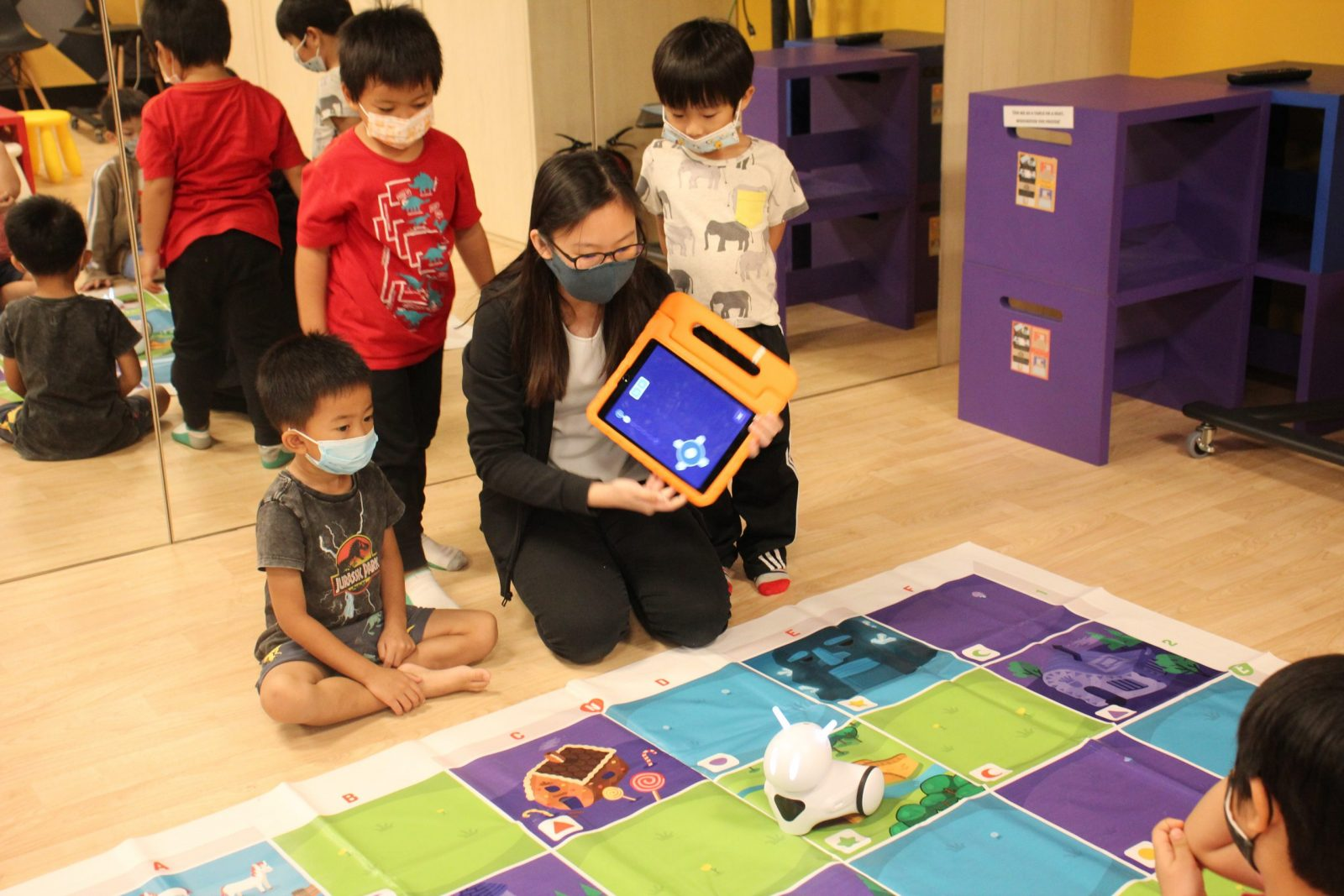 Educator holding an iPad with junior coders surrounding her and in front of Photon robot