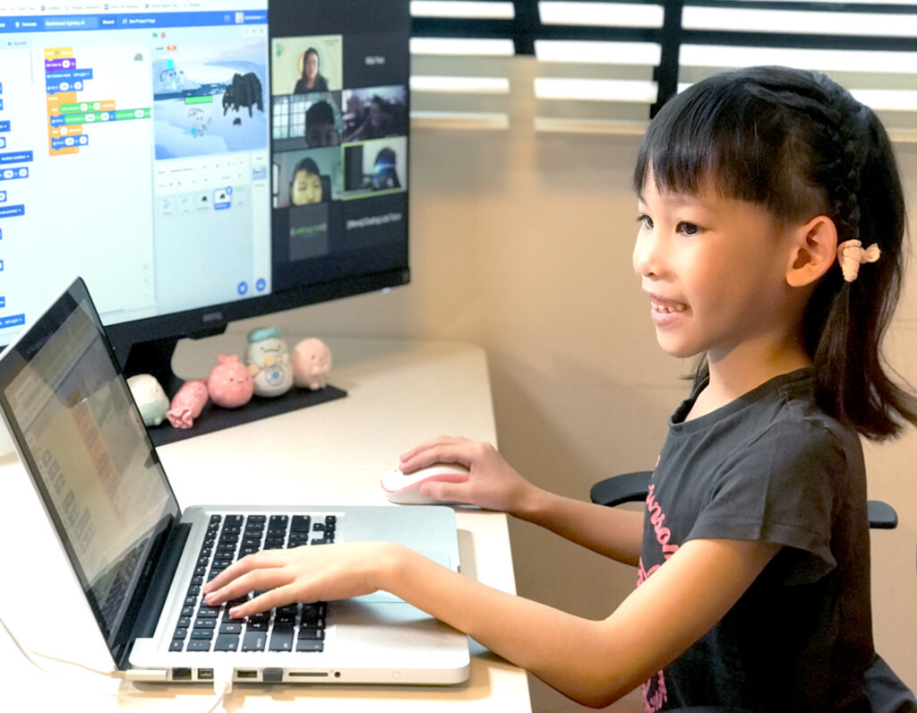 Audrey using a laptop at home as she attends our LIVE Home-Based Learning classes