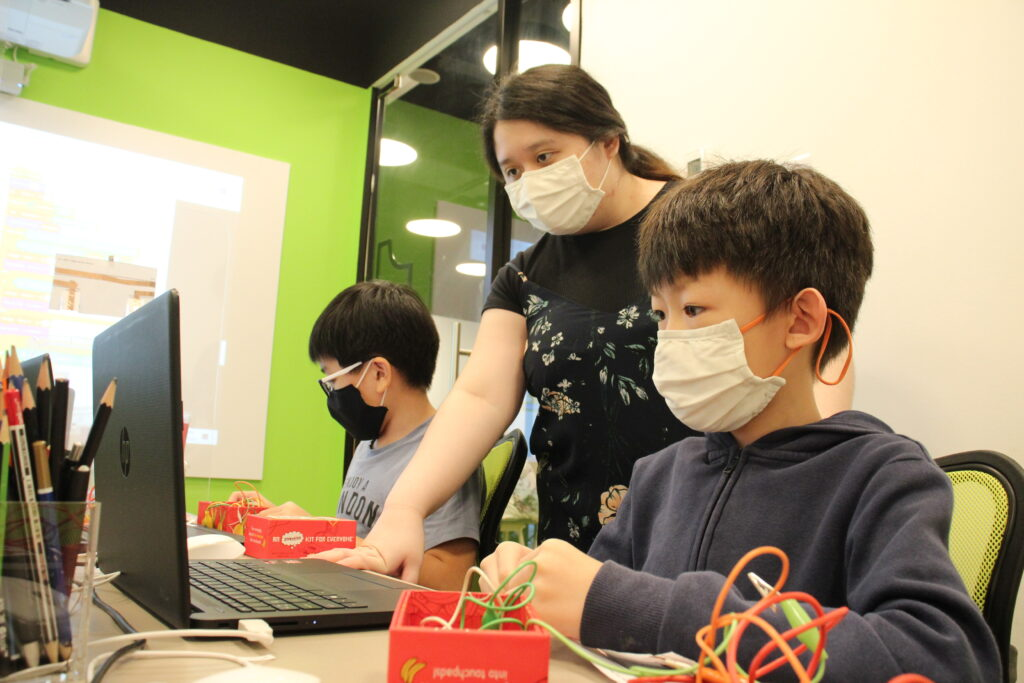 Rachel and two students tinkering with Makey Makey